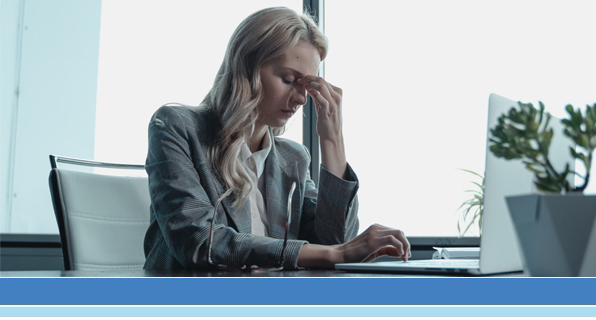 woman at desk looking stressed